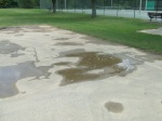 A closer view of the asphalt surface of the basketball courts and the puddle-filled depressions on the court, Meadowbrook Park, September 17, 2010 (Donald Earl Collins)