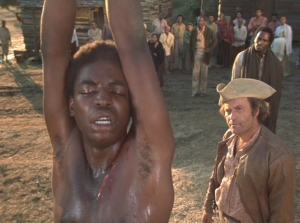 Kunta Kinte being whipped, Roots (1977) screenshot, July 6, 2012. (http://irvine.wikis.gdc.georgetown.edu). Qualifies as fair use under US Copyright laws because of screenshot's low resolution.