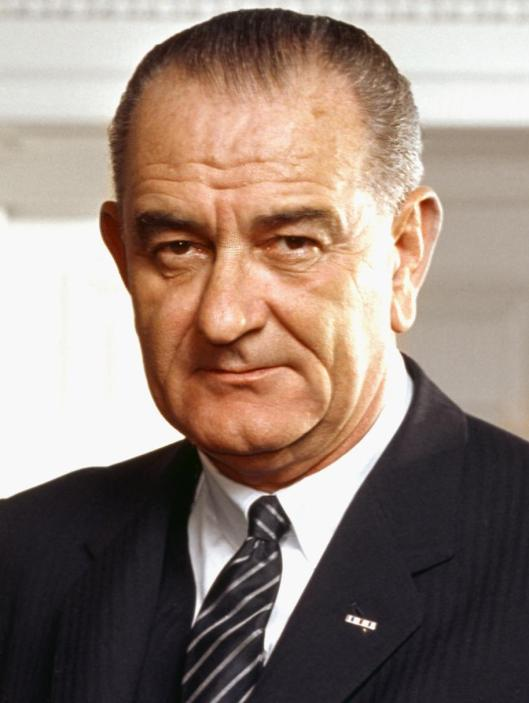 Photo portrait of President Lyndon B. Johnson [our last transformational President] in the Oval Office, leaning on a chair, March 10, 1964. (Arnold Newman, White House Press Office via Wikipedia). In public domain.