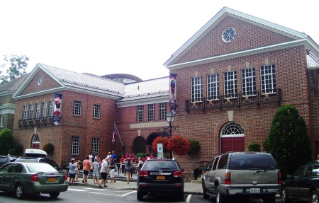 The front entrance to the National Baseball Hall of Fame and Museum, Cooperstown, NY, July 15, 2012. (Beyond My Ken via Wikipedia). Released to public domain via Creative Commons 3.0.