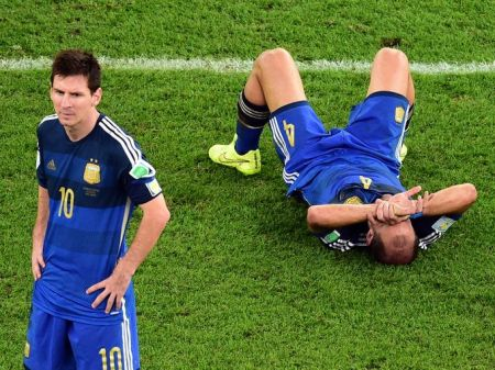 Argentina's Pablo Zabaleta lies on the pitch as Lionel Messi stands beside him after losing to Germany in the final, Rio de Janeiro, Brazil, July 13, 2014. (Francois Xavier Marit/AP via http://usatoday.com).
