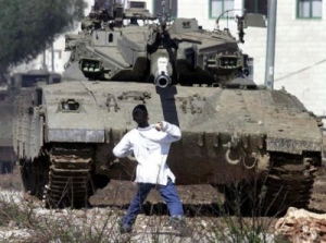 Faris Odeh throws a stone at an Israeli tank near the Israel-Gaza border, October 29, 2000, during the 2nd Palestinian Intifada (ten days before the IDF gunned him down in Gaza). (http://socialistworker.org).