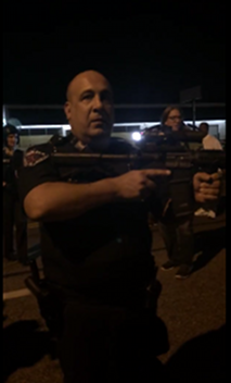 """Officer Go Fuck Yourself"" aiming rifle at protestors and journalists, Ferguson, MO, August 19, 2014. (http://www.deathandtaxesmag.com/)."