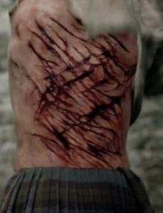 "Outlander character Jamie Fraser in midst of second 100-slashes punishment, screenshot (cropped) from S1:Episode 06 ""The Garrison Commander,"" September 13, 2014. (http://plus.google.com)."