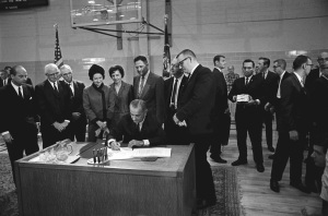 President Lyndon Johnson signing the Higher Education Act of 1965, Master's Gymnasium, Texas State University, San Marcos, TX, November 8, 1965. (http://smmercury.com/). In public domain.