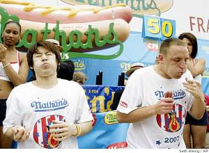 Takeru Kobayashi and Joey Chestnut battle it out at the 2007 Nathan's Famous Fourth of July Hot Dog Eating Contest, Coney Island, Brooklyn, NY, July 4, 2007. (Seth Wenig/AP; http://philly.com).