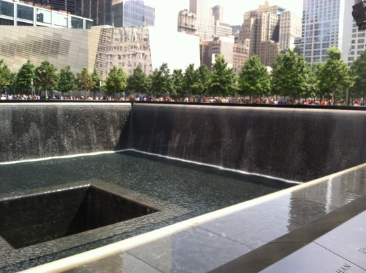 9/11 Memorial reflecting pool (w/ reflection of Freedom Tower off building straight ahead), August 5, 2014. (Donald Earl Collins).