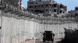 Israeli armored car patrolling barrier wall between it and Palestinian West Bank, June 17, 2016. (http://presstv.ir).